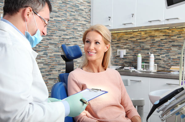 Woman talking to dentist during dental exam from Sparkle Dental Boston